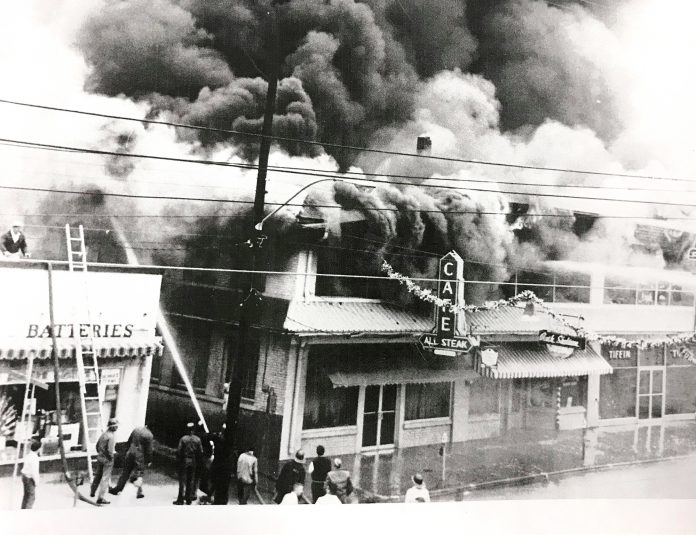 In 1962, the businesses next to Bennett Auto Supply caught fire and burned down. The fire began in what was once the theater and destroyed the block, including the original All Steak Cafe. The alley, which still exists on the south side of Bennett, kept the fire from spreading. This photo shows a young Doug Bennett on the roof of the building working to prevent the fire from spreading as the fire department fought the blaze. (Bennett family)